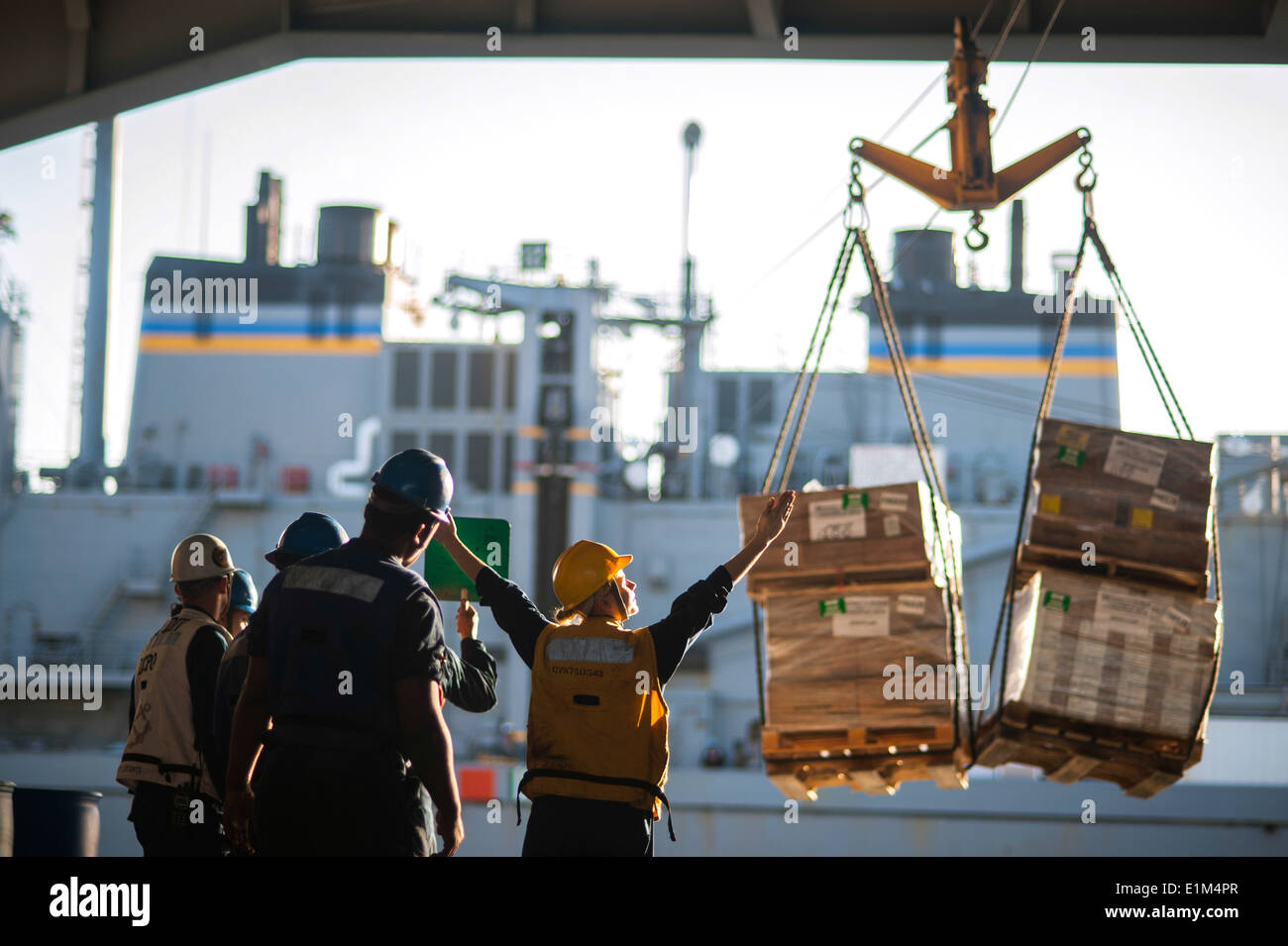 U.S. Sailors guide pallets from the fast combat support ship USNS Arctic (T-AOE 8) to the hangar bay of the aircraft carrier US - Stock Image