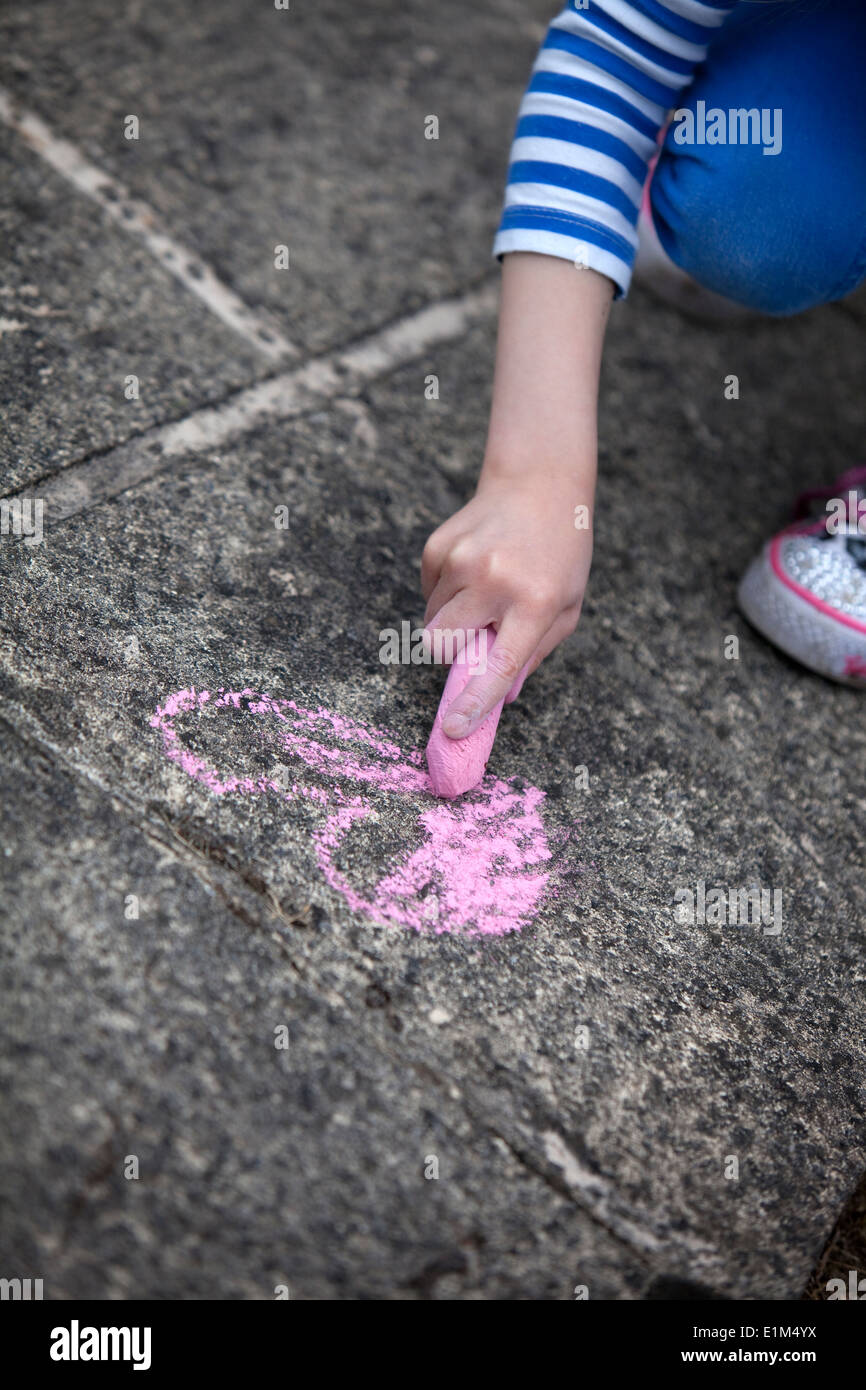 Child drawing a pink chalk heart on a concrete sidewalk. - Stock Image