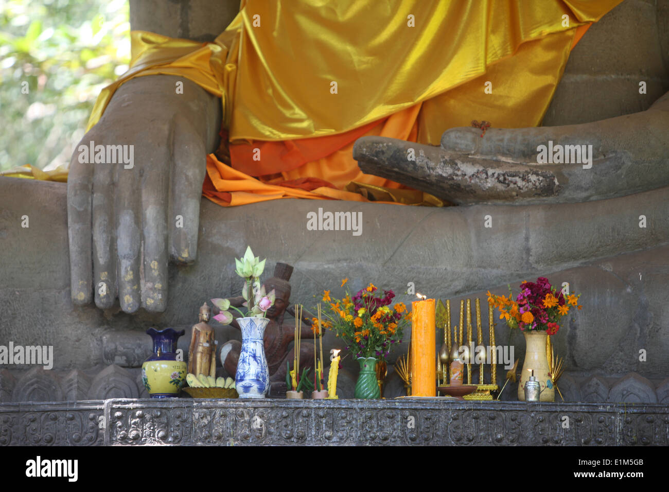 Buddha statue with offerings. The Buddha shown in earth-touching position. - Stock Image