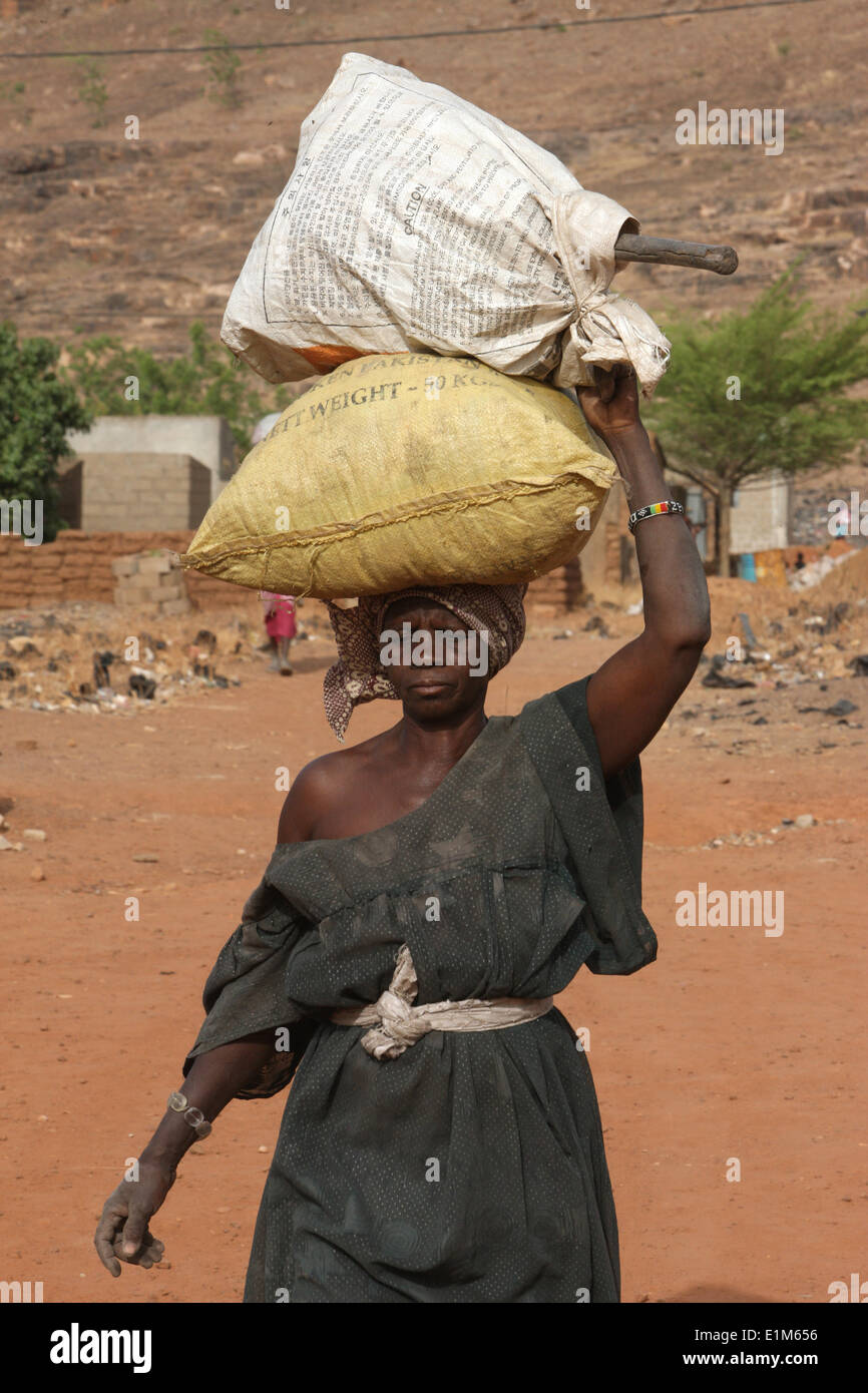 Woman carrying sacks on her head Stock Photo