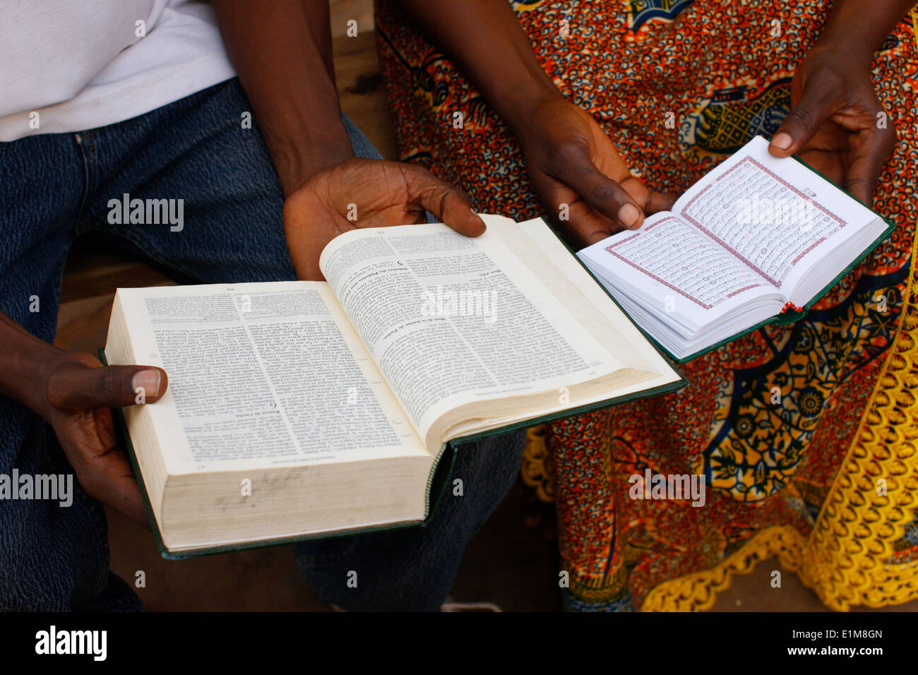 Africans reading the Bible and the Koran. - Stock Image