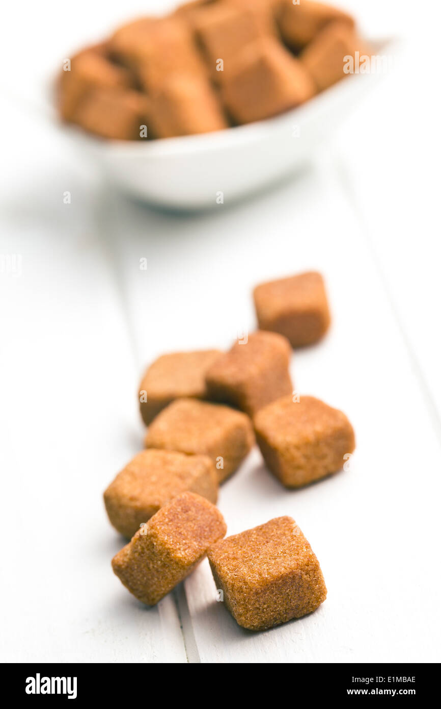 brown sugar cubes on white wooden table - Stock Image