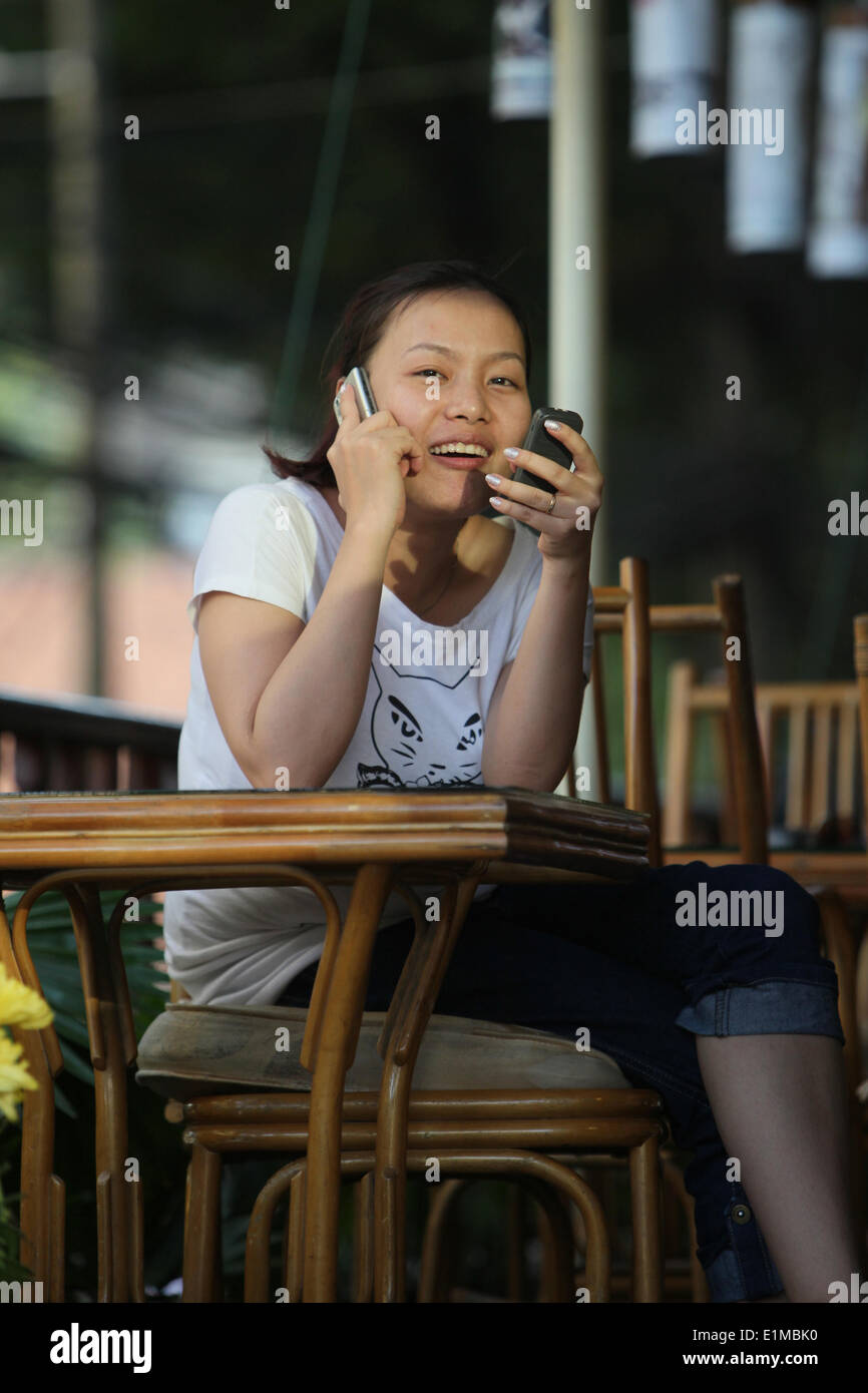 Young girl with two telephones. - Stock Image