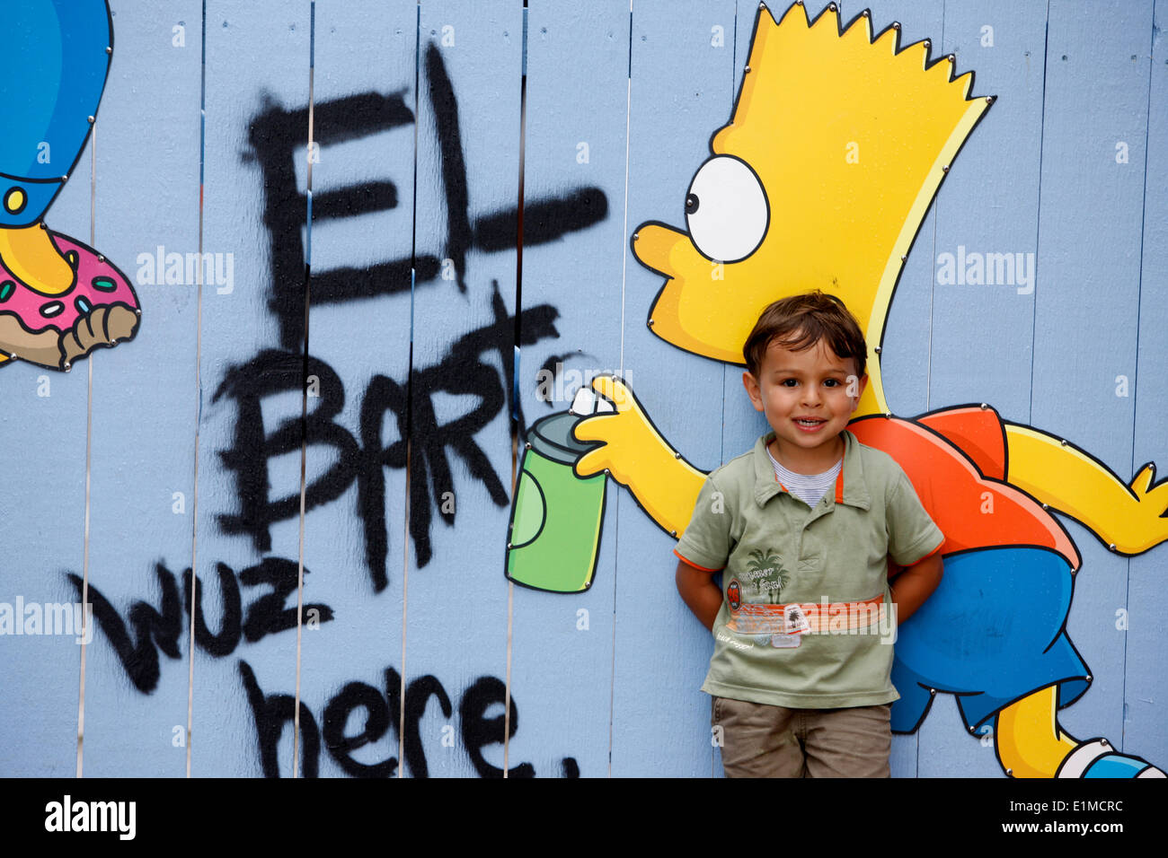 Boy standing in front of a Bart Simpson mural at Universal Orlando - Stock Image