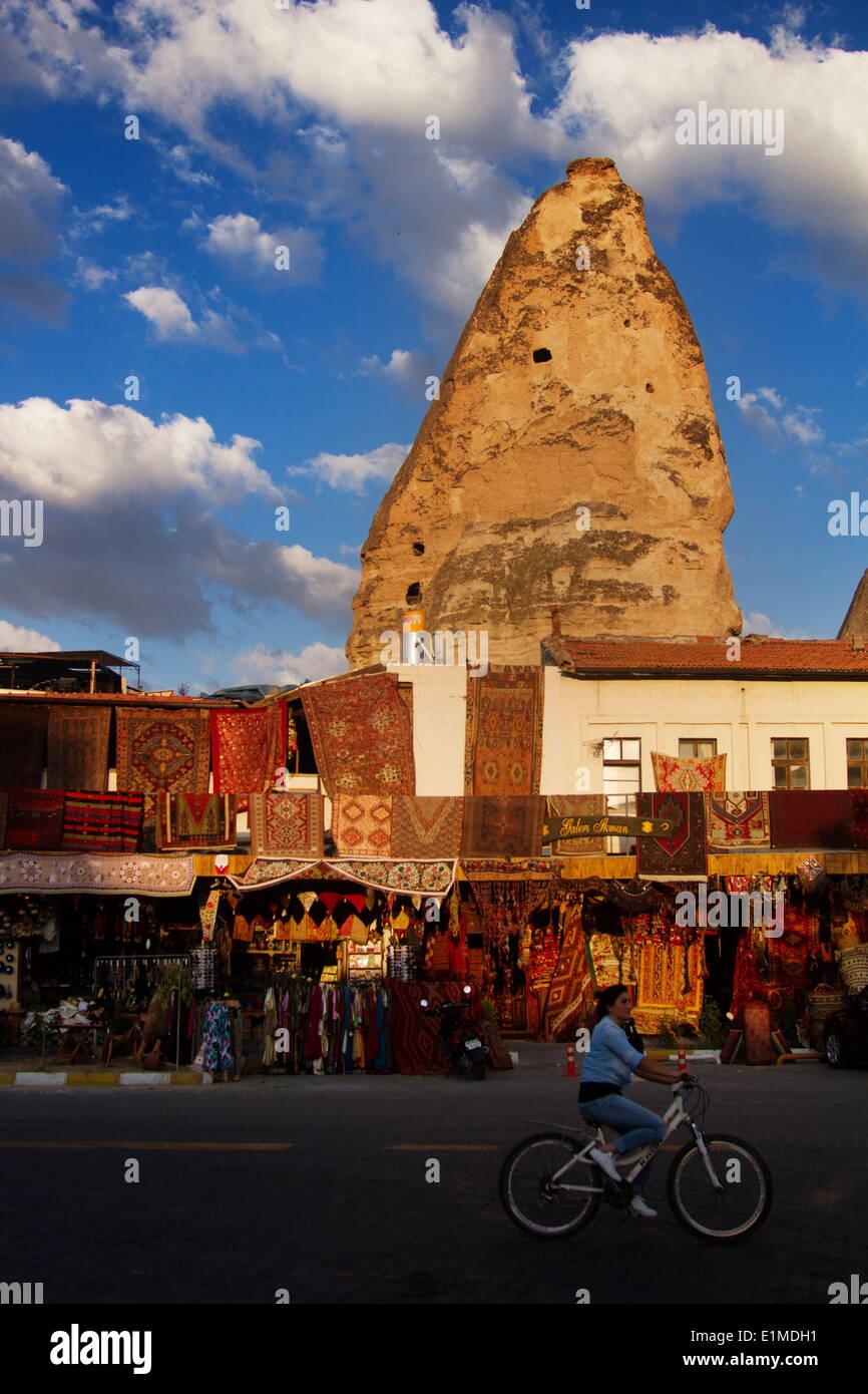 Turkey; Cappadocia; Anatolia; Göreme; Sunset; People; Girl; Bicycle; Shop; Present; Sun; House; Carpet - Stock Image
