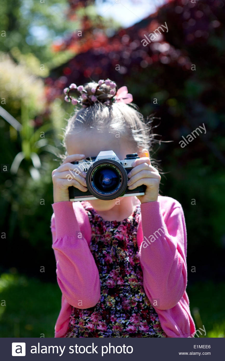 Girl taking a photograph on an old film SLR camera - Stock Image