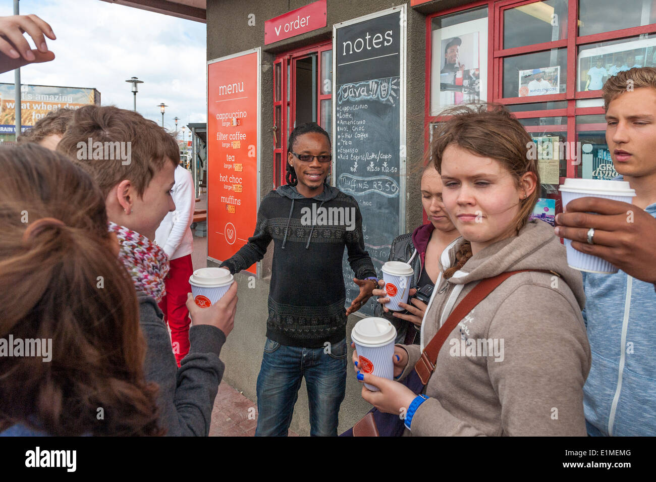 German students and township tour guide at a coffee shop in Khayelitsha, Cape Town, South Africa - Stock Image