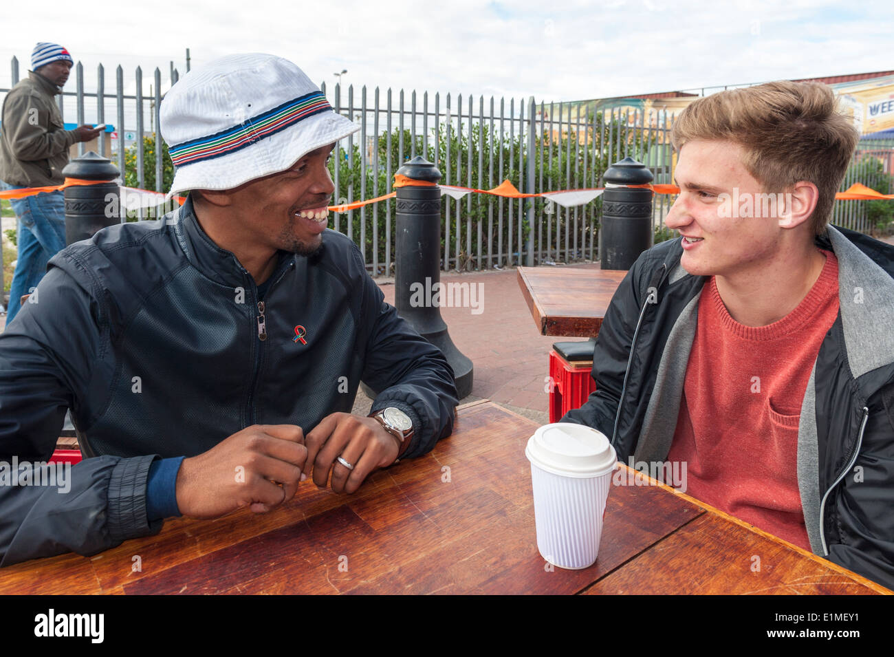 German student chats with a township travel guide in Khayelitsha, Cape Town, South Africa - Stock Image