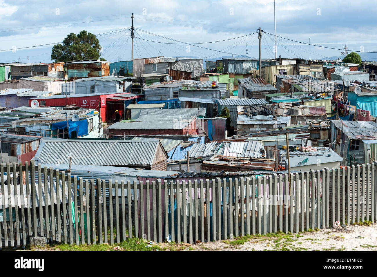 Corrugated iron sheds behind a fence in Khayelitsha, Cape Town, South Africa - Stock Image