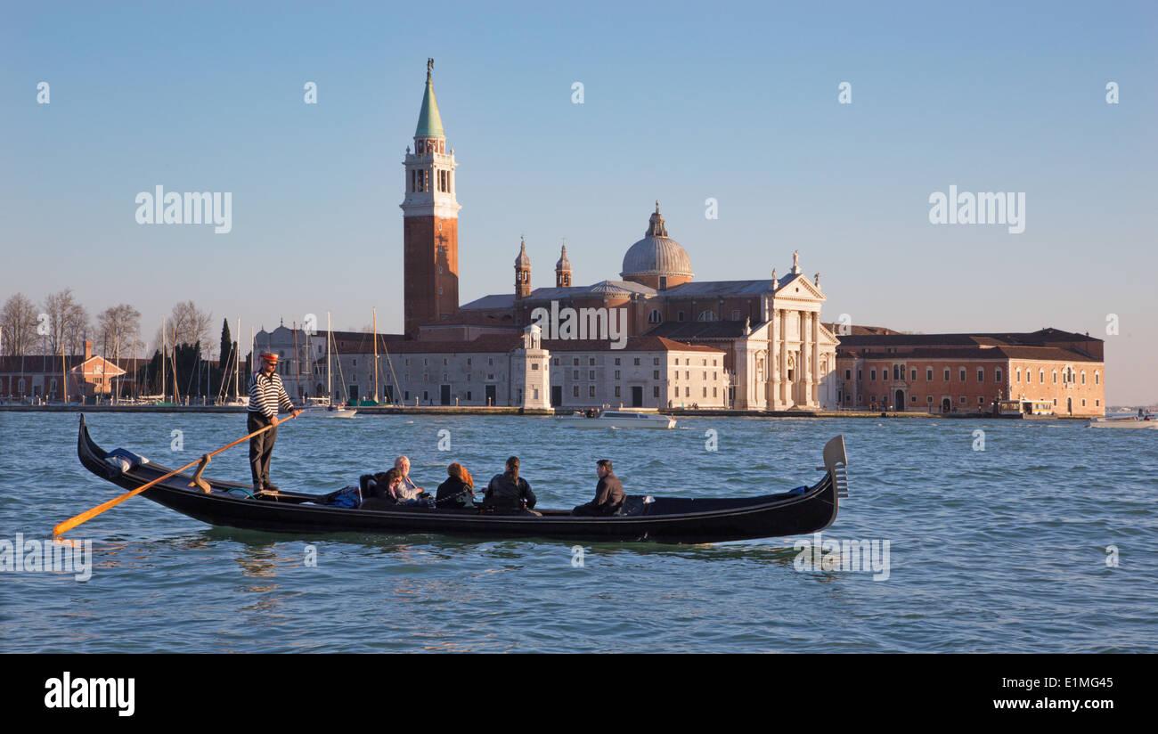 VENICE, ITALY - MARCH 14, 2014: Gondolier on the lagoon and San Giorgio Maggiore church in evening light - Stock Image