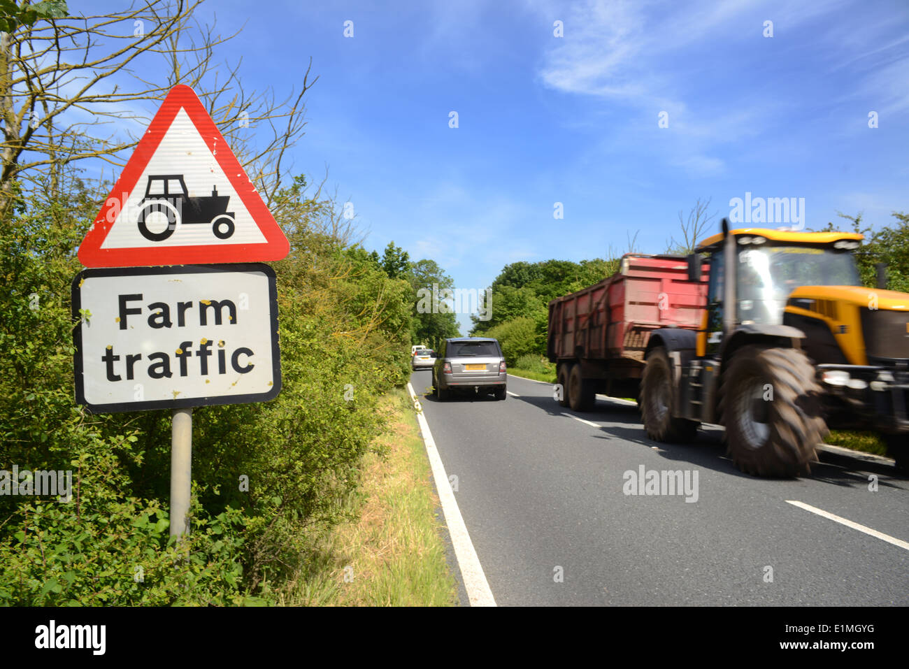 tractor and trailer passing warning sign of farm traffic in road ahead yorkshire united kingdom - Stock Image