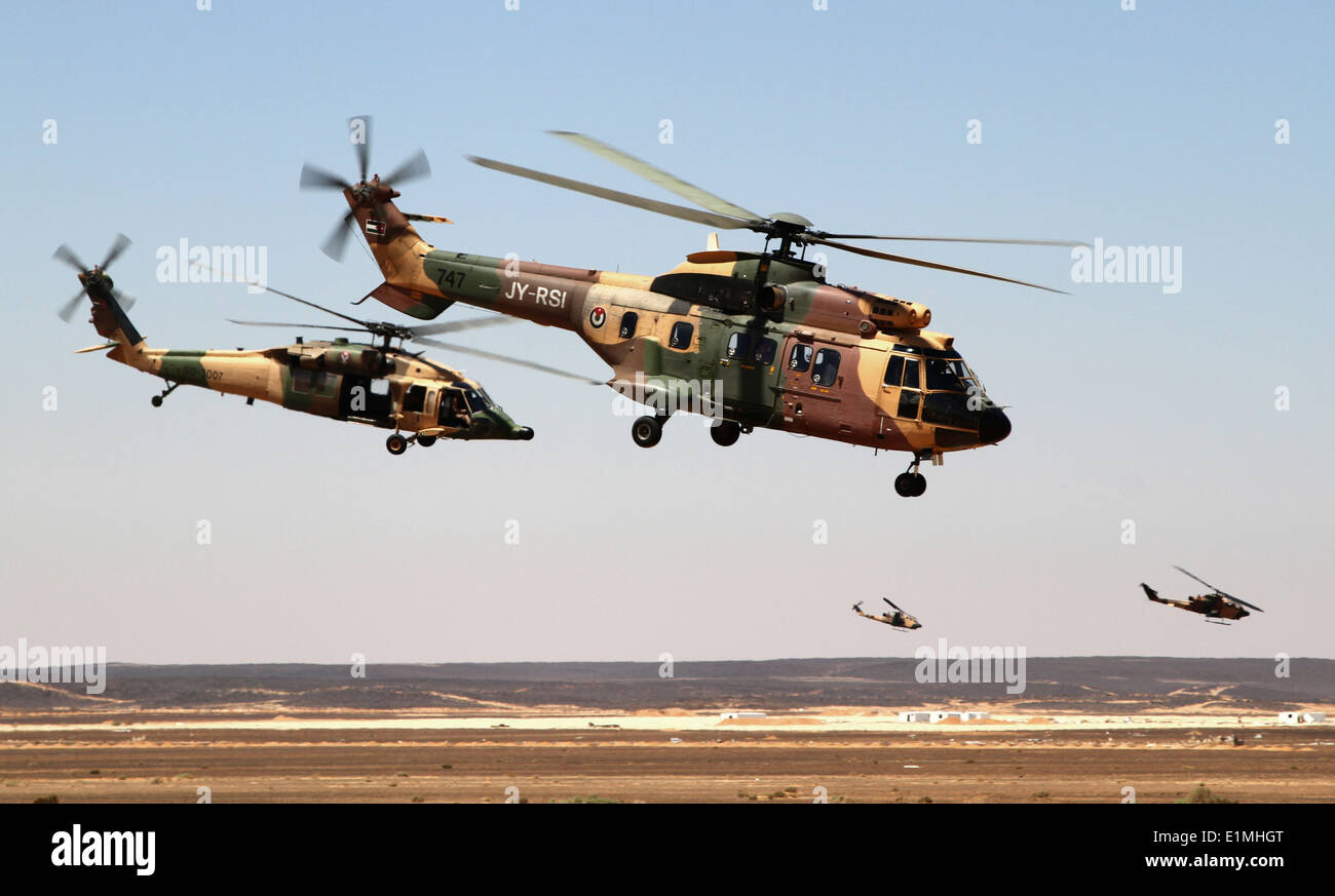 Royal Jordanian Air Force AS332 Super Puma and AH-1 Cobra helicopters fly away after dropping off special operations forces ser - Stock Image
