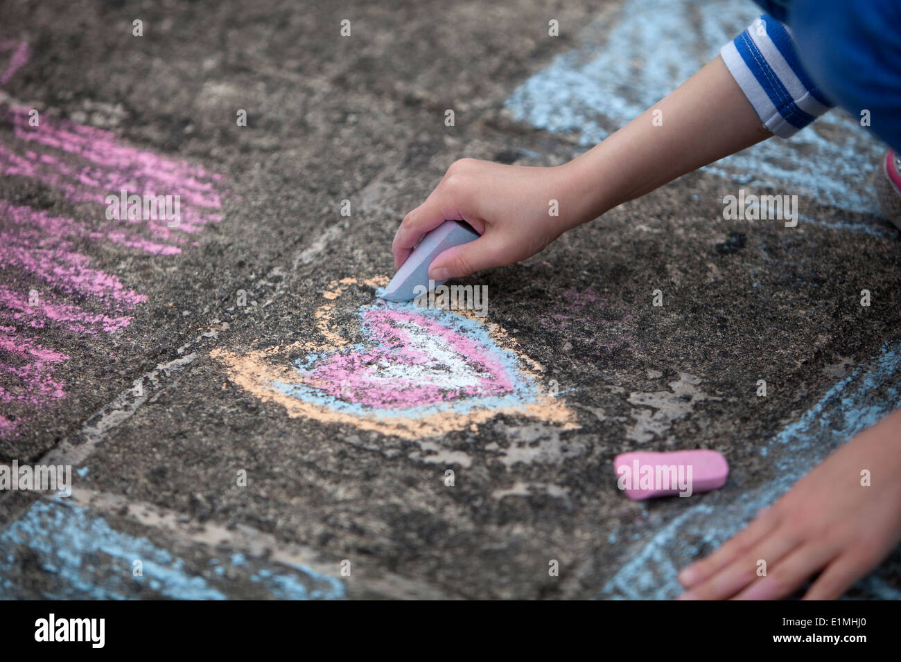Young child drawing a colorful chalk heart on a stone sidewalk. - Stock Image