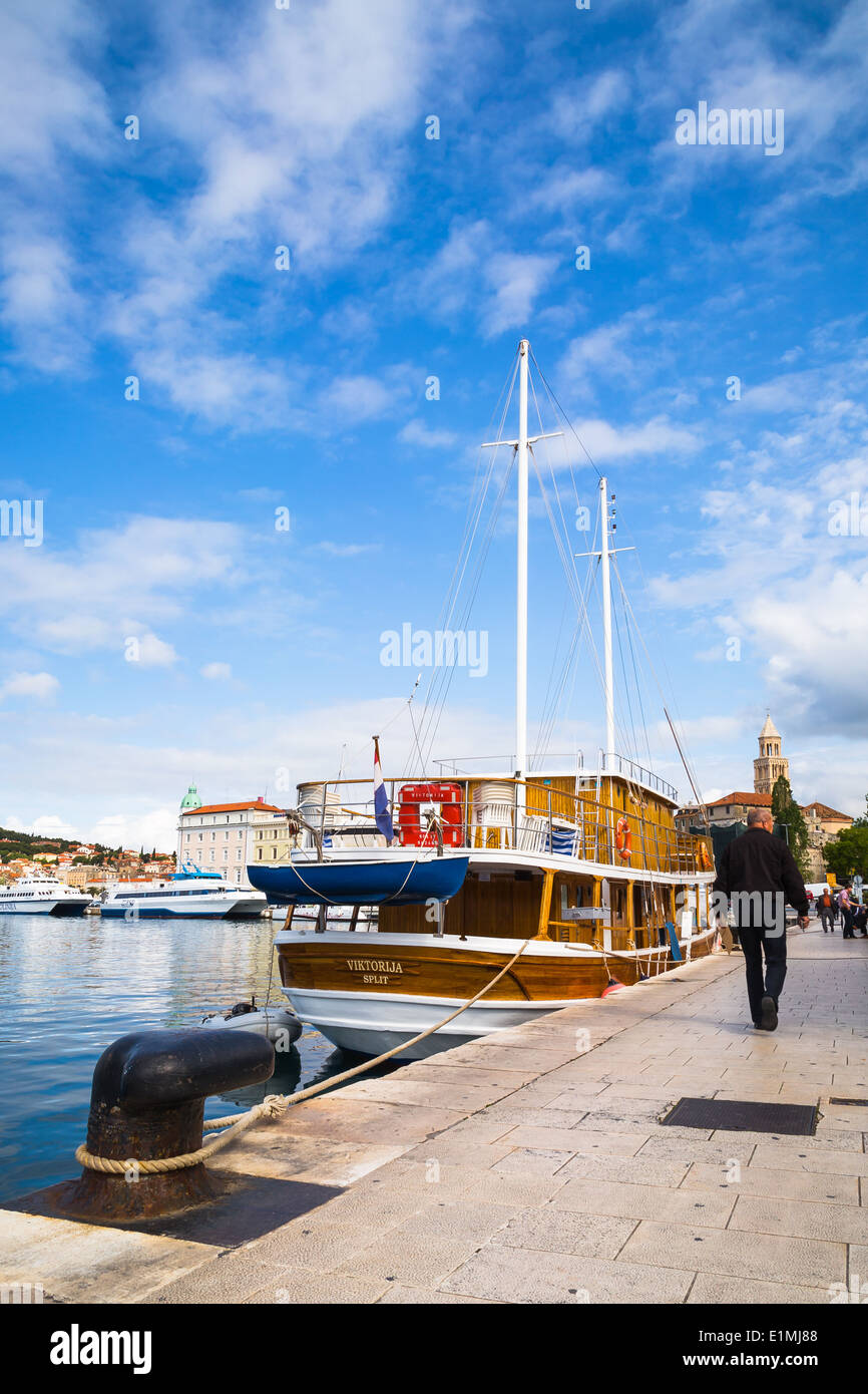 A man is seen walking past a boat on the approach to Split Riva in Dalmatia Croatia - Stock Image
