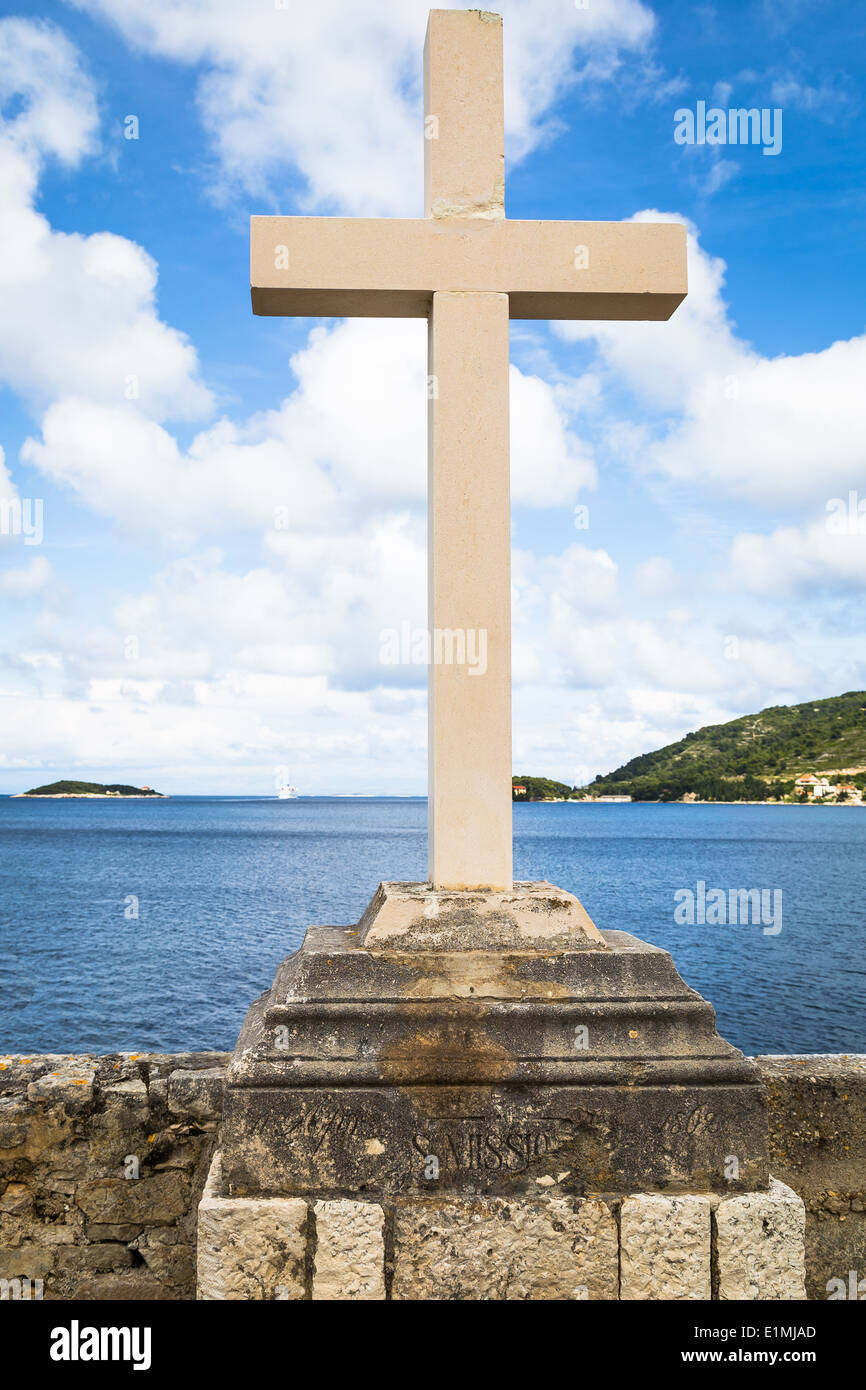 a christian cross is seen against a cloudy sky and islands at the entrance to vis harbour in dalmatia croatia - Stock Image