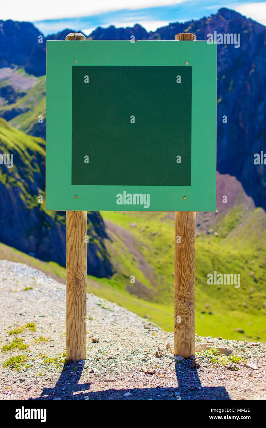 Board with textspace on mountains background. - Stock Image