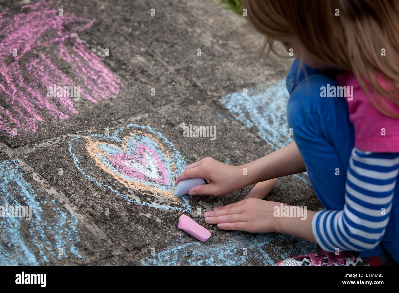 Girl drawing a chalk heart on a concrete sidewalk. - Stock Image