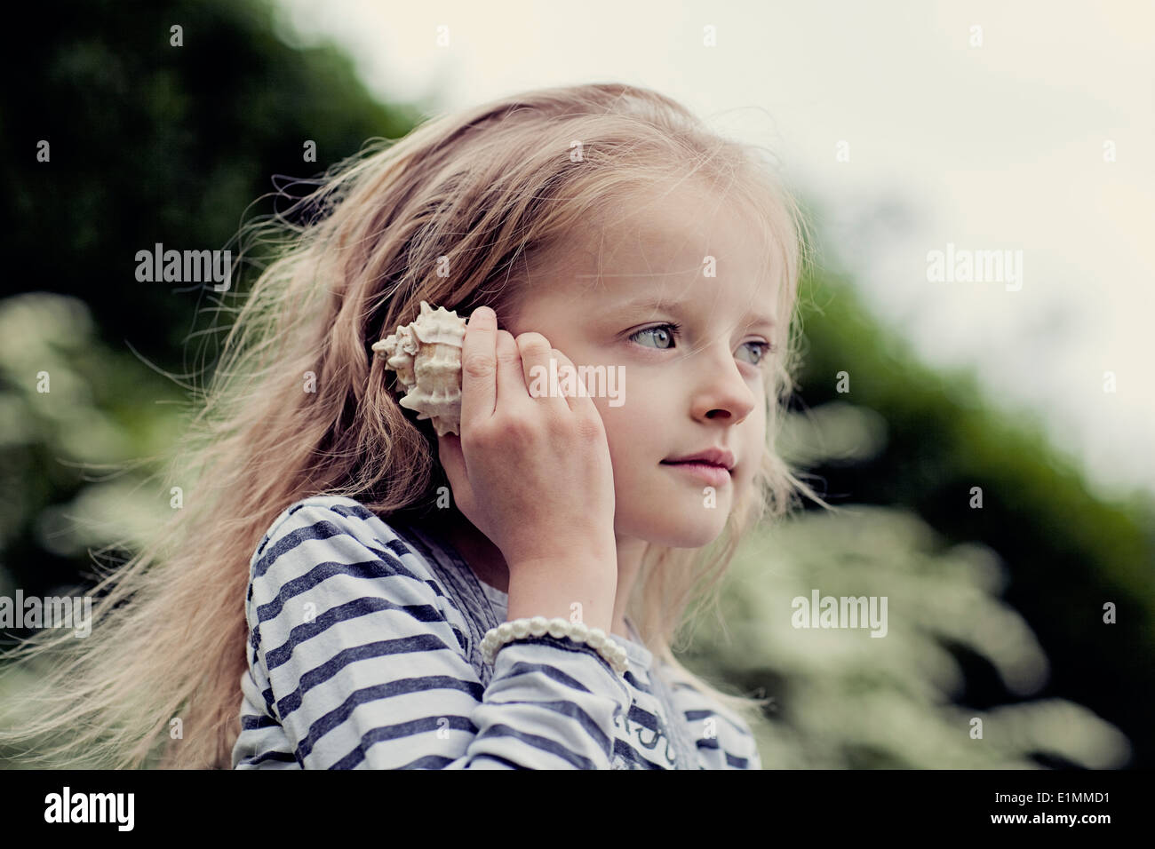 Child listening to the sounds of a seashell. Stock Photo