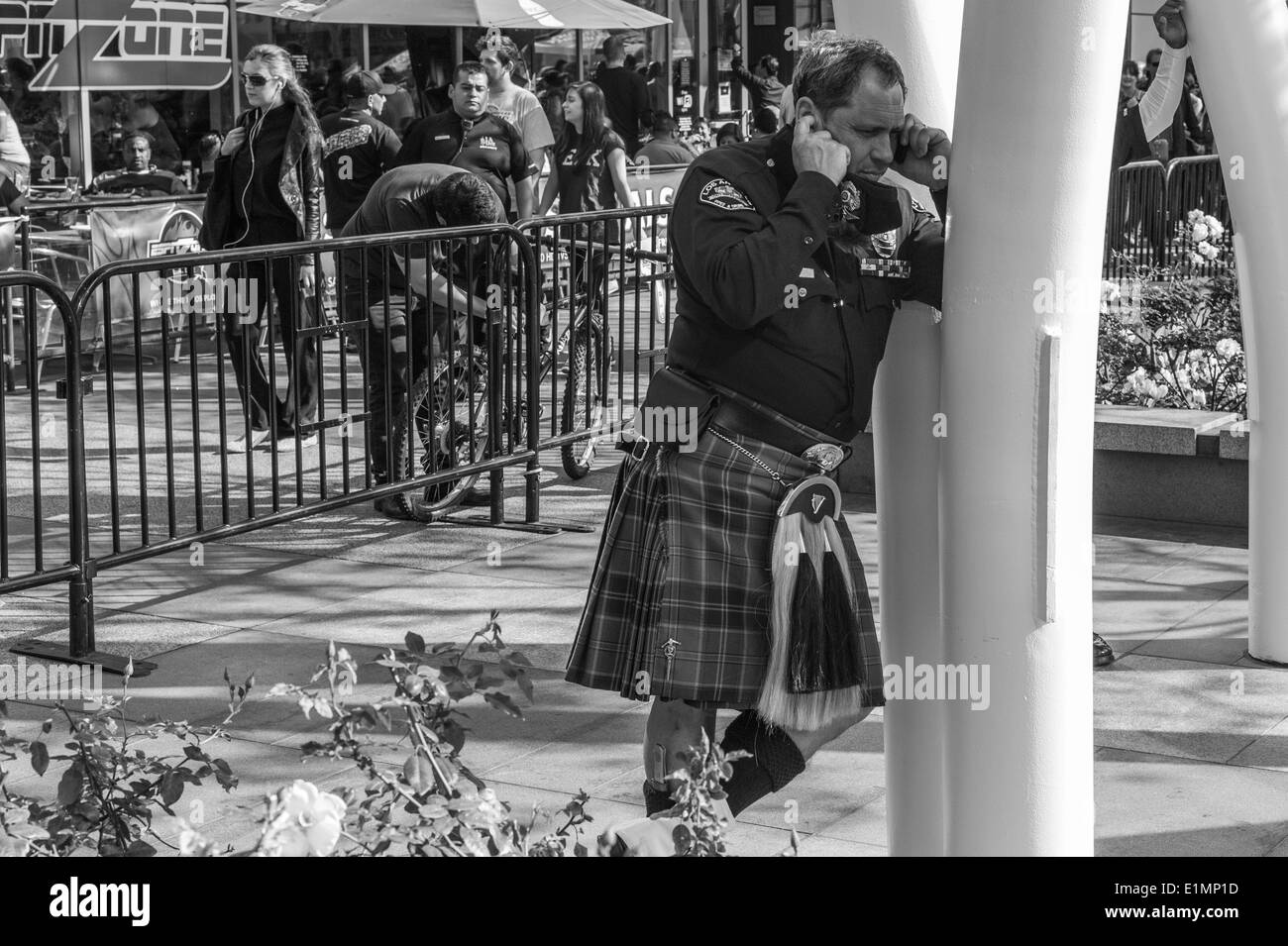 Los Angeles Police Officer talking on mobile phone wearing kilt on St. Patrick's Day. - Stock Image