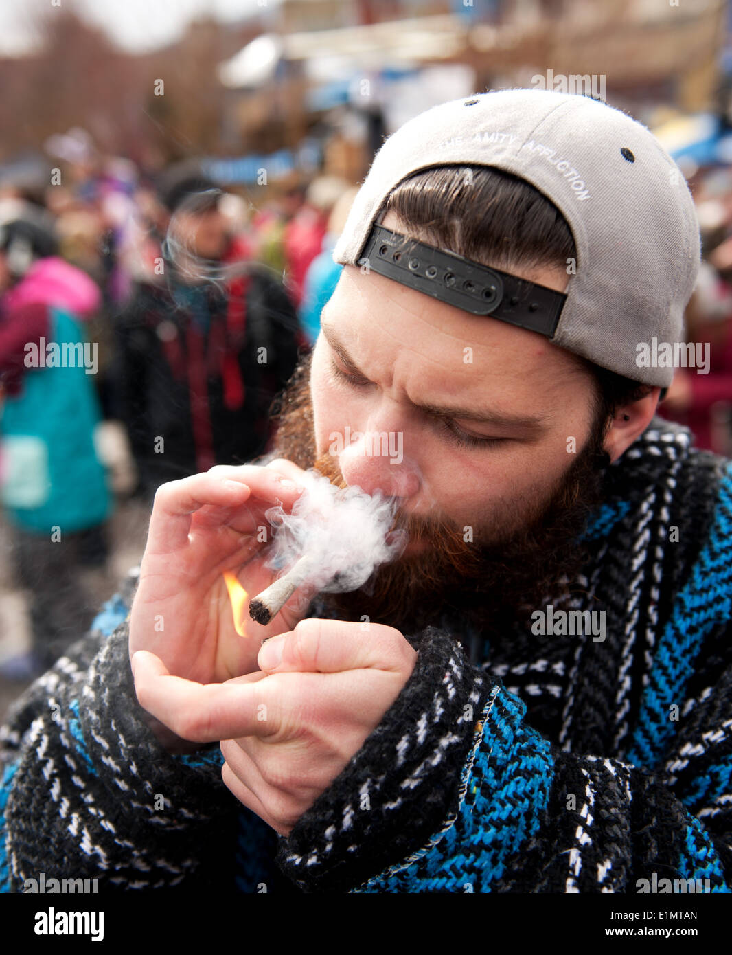 A man lights a marijuana cigarette, or joint, during a 420 day celebration in the Whistler village. Whistler BC, Canada. - Stock Image