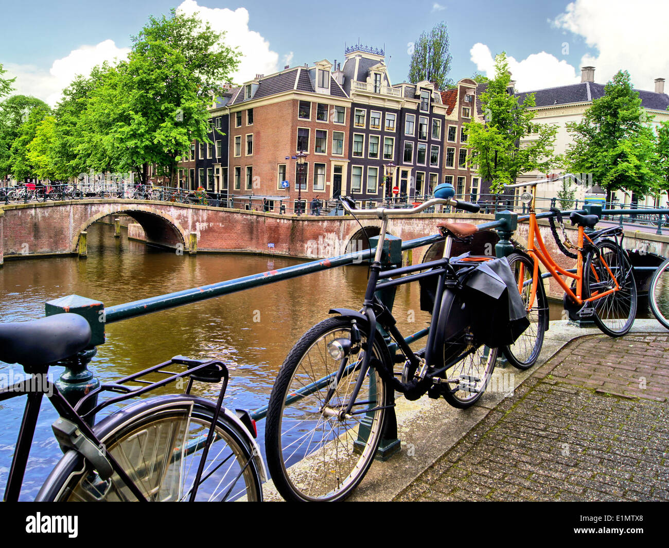 Amsterdam canal scene with bicycles and bridges - Stock Image