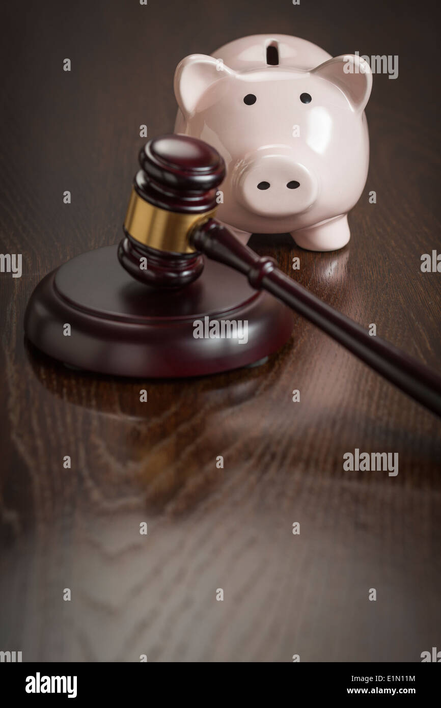 Gavel and Piggy Bank on Reflective Wooden Table. - Stock Image