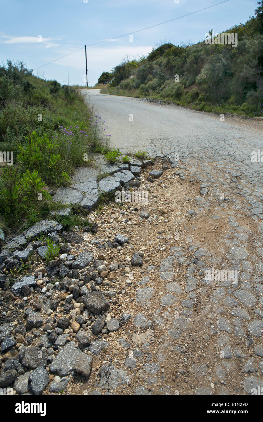 A damaged road in Greece showing cracked tarmac Stock Photo