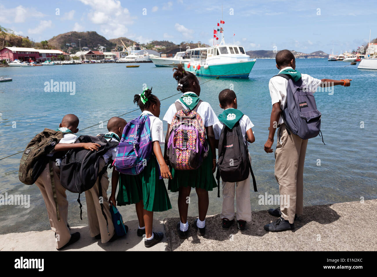 Six school children standing on the harbour walkway and looking out to the Carenage marina, St George, Grenada, West Indies - Stock Image