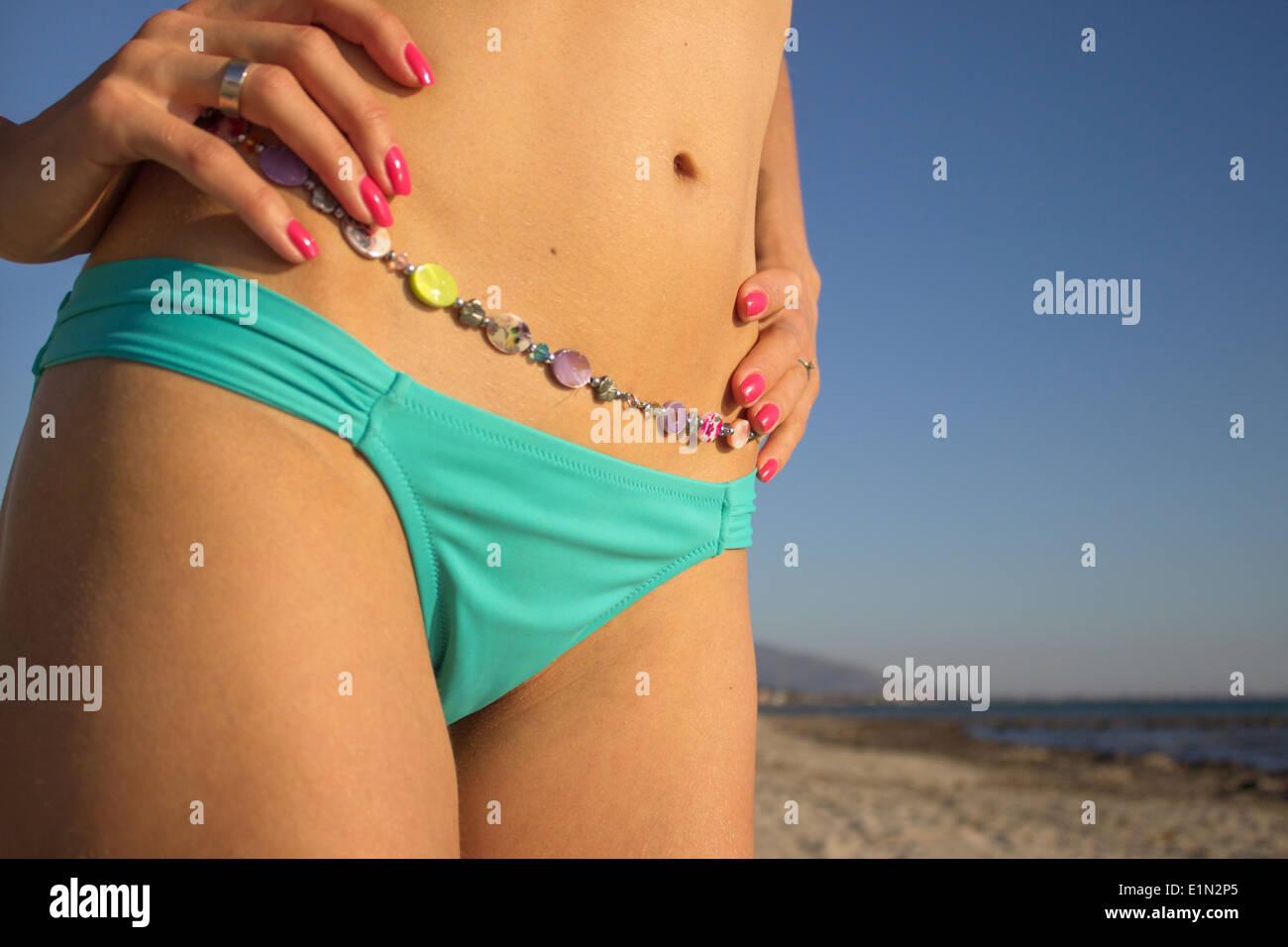 woman 'bikini bottom' body colorful closeup vivid colors colours 'hands on hips' detail slim bright beautiful  sea coast beach - Stock Image