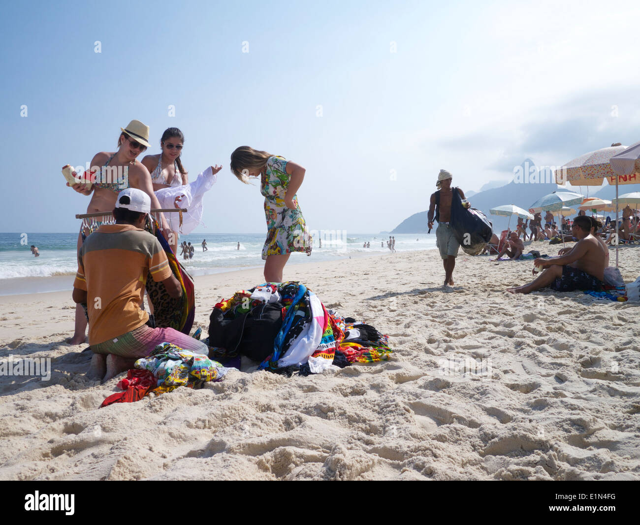 RIO DE JANEIRO, BRAZIL - CIRCA MARCH, 2013: Customers try on merchandise from a vendor in a typical scene on Ipanema Beach. - Stock Image