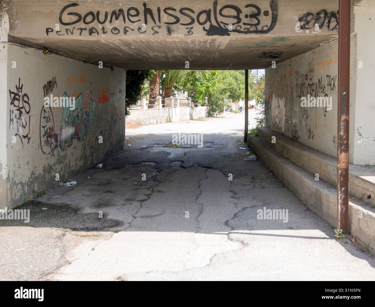 Dangerous looking underpass with rubbish and graffiti - Stock Image