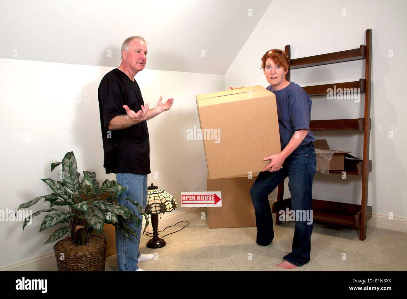 Woman carrying heavy boxes with man gesturing in room of their new home Stock Photo