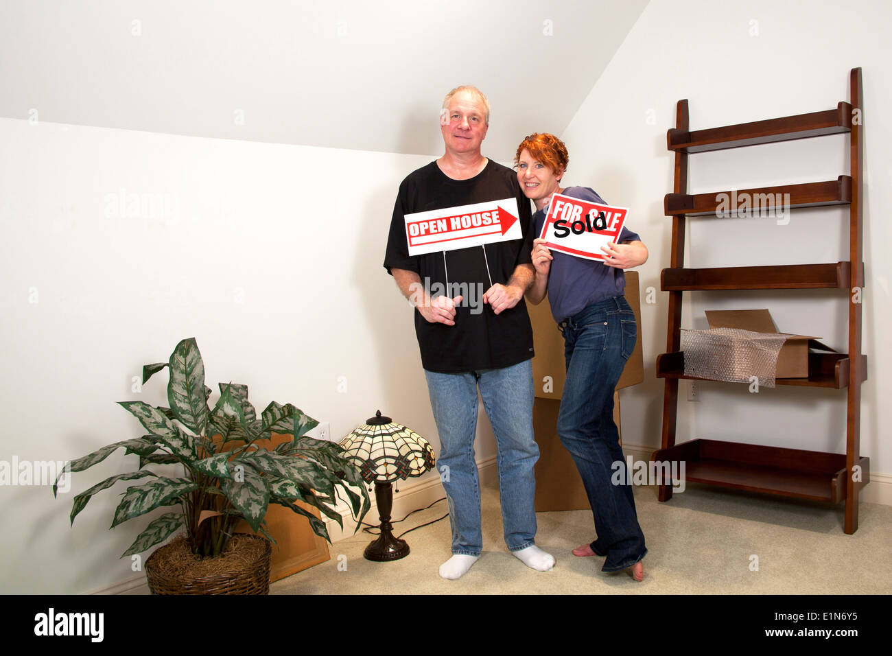 Man and woman standing in their new home holding real estate signs Stock Photo
