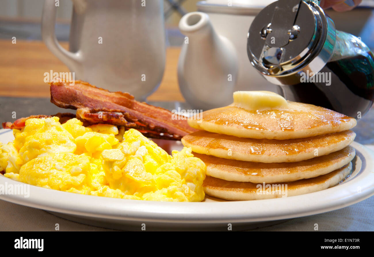 Breakfast of pancakes, scrambled eggs and bacon on a white ...