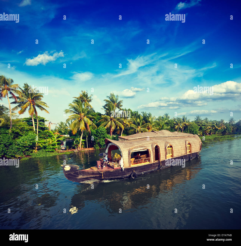 Vintage retro hipster style travel image of Kerala travel tourism background - houseboat on Kerala backwaters. Kerala, - Stock Image