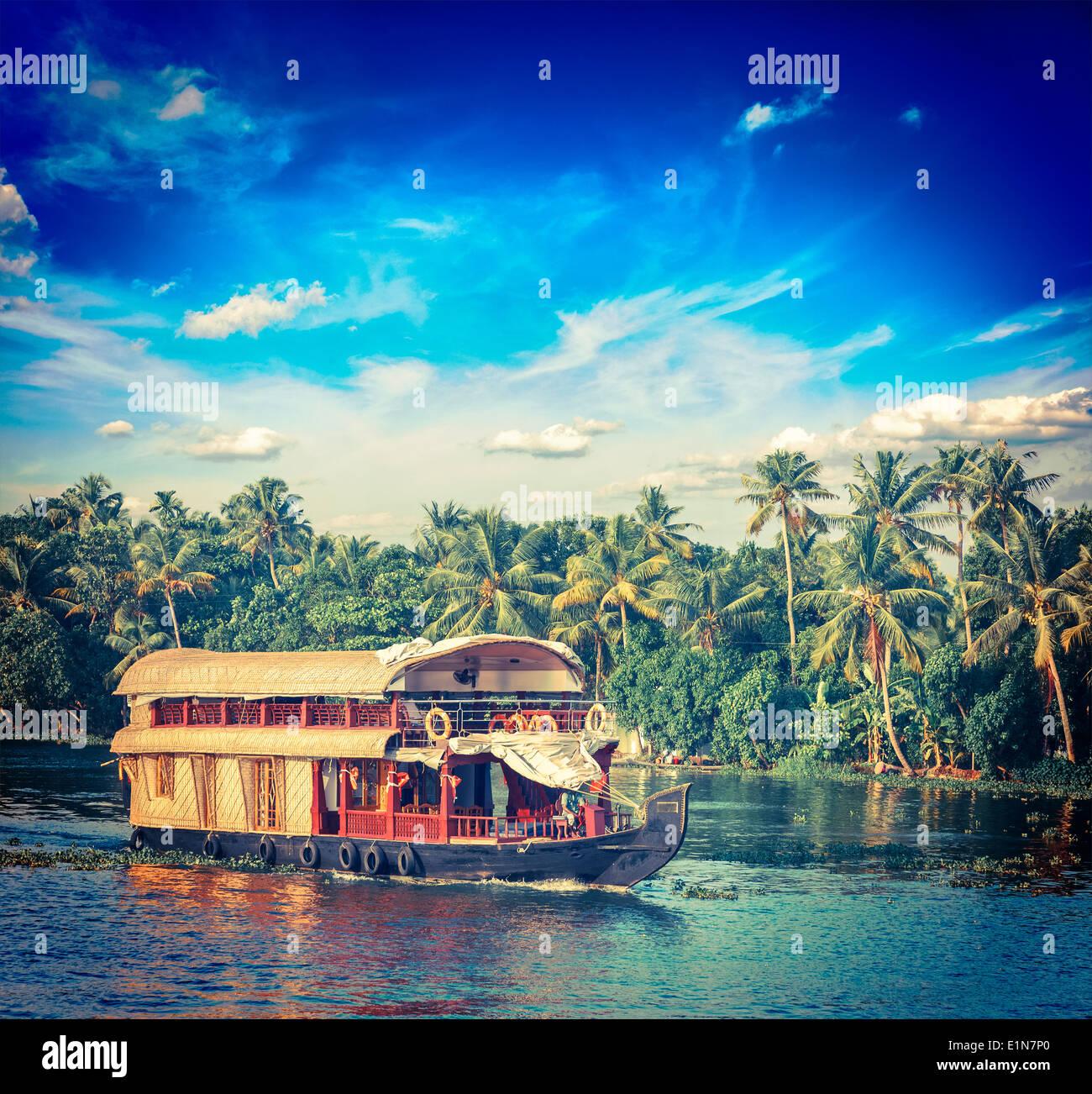 Vintage retro hipster style travel image of Kerala travel tourism background - houseboat on Kerala backwaters. Kerala, India - Stock Image
