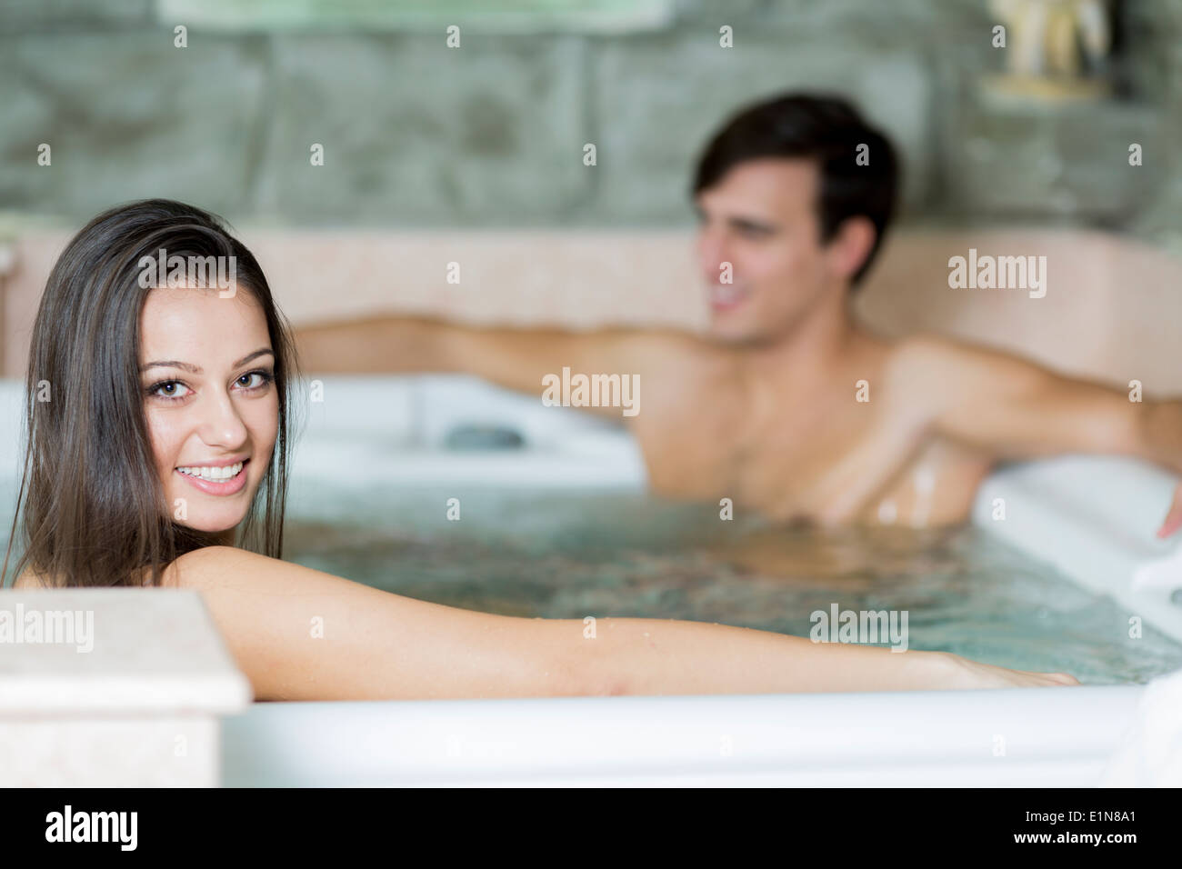 Young couple relaxing in the hot tub - Stock Image