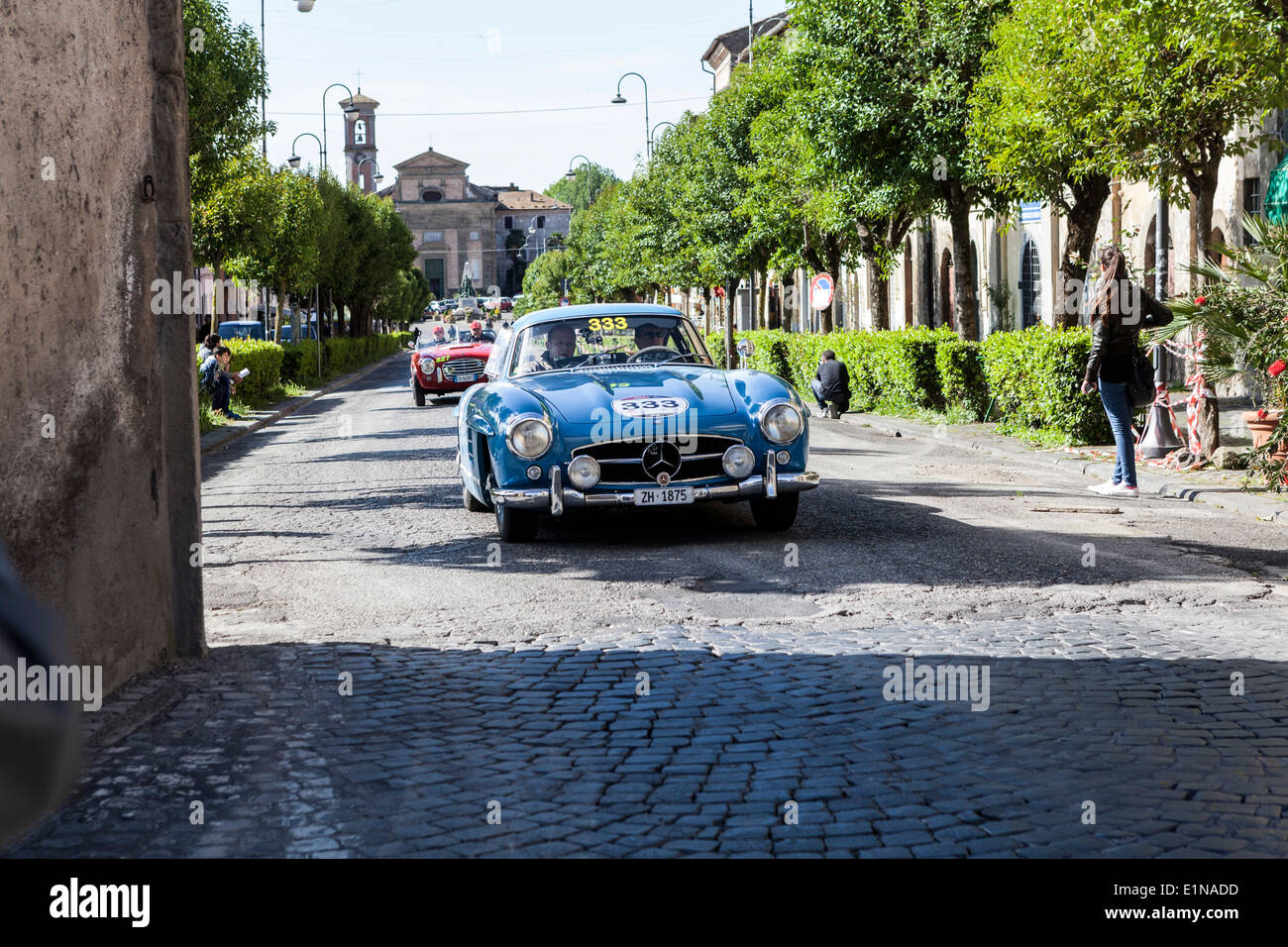 A 1955 Mercedes-Benz 300 SL W 198 followed by an Italian S.I.A.T.A. Daina Gran Sport pass through Ronciglione in the 1000 miglia - Stock Image