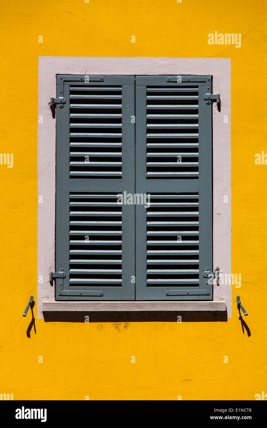 Grey shutters on a bright yellow wall in Sion, Switzerland - Stock Image