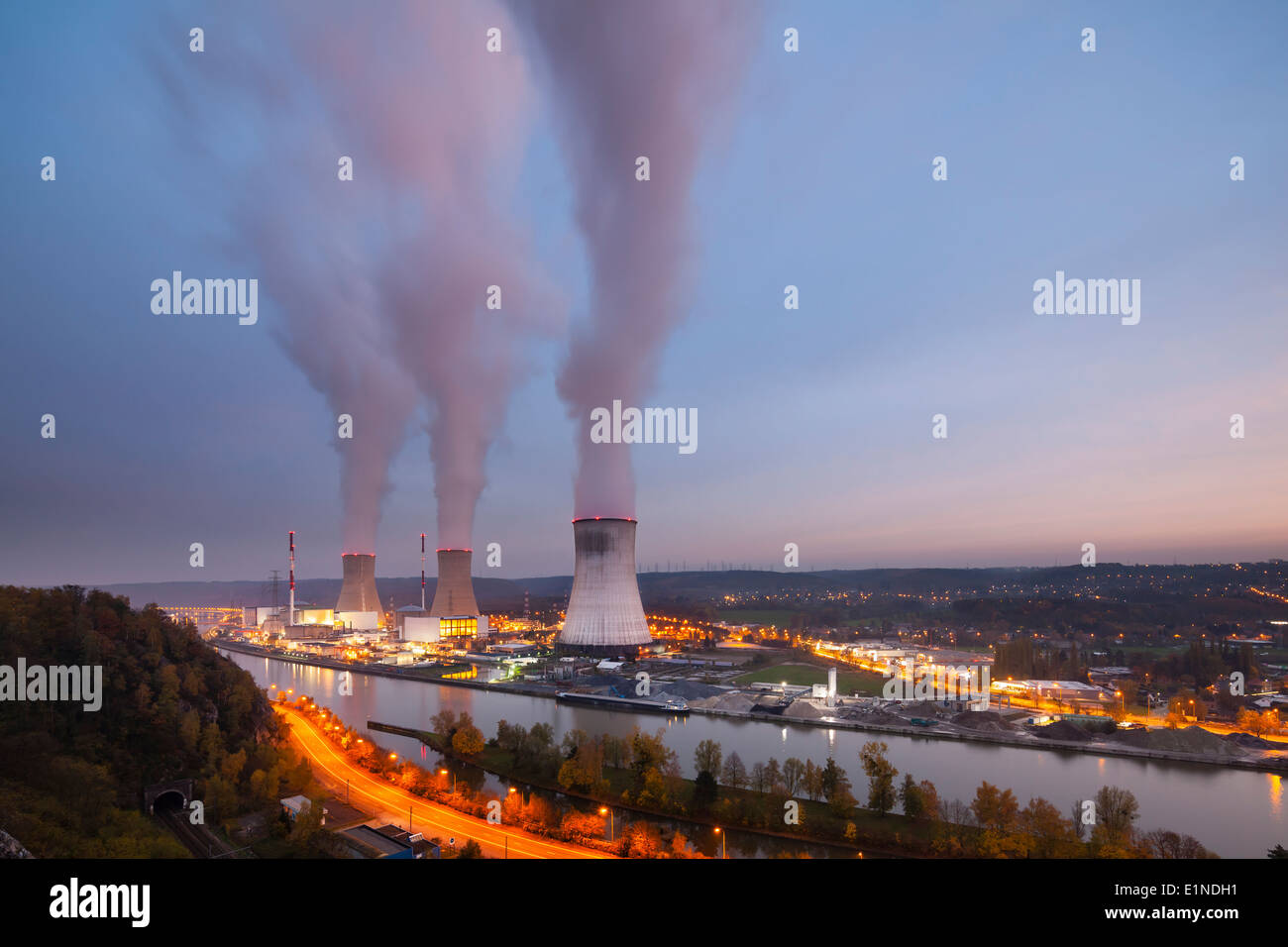 A large nuclear power station by a river at dusk - Stock Image