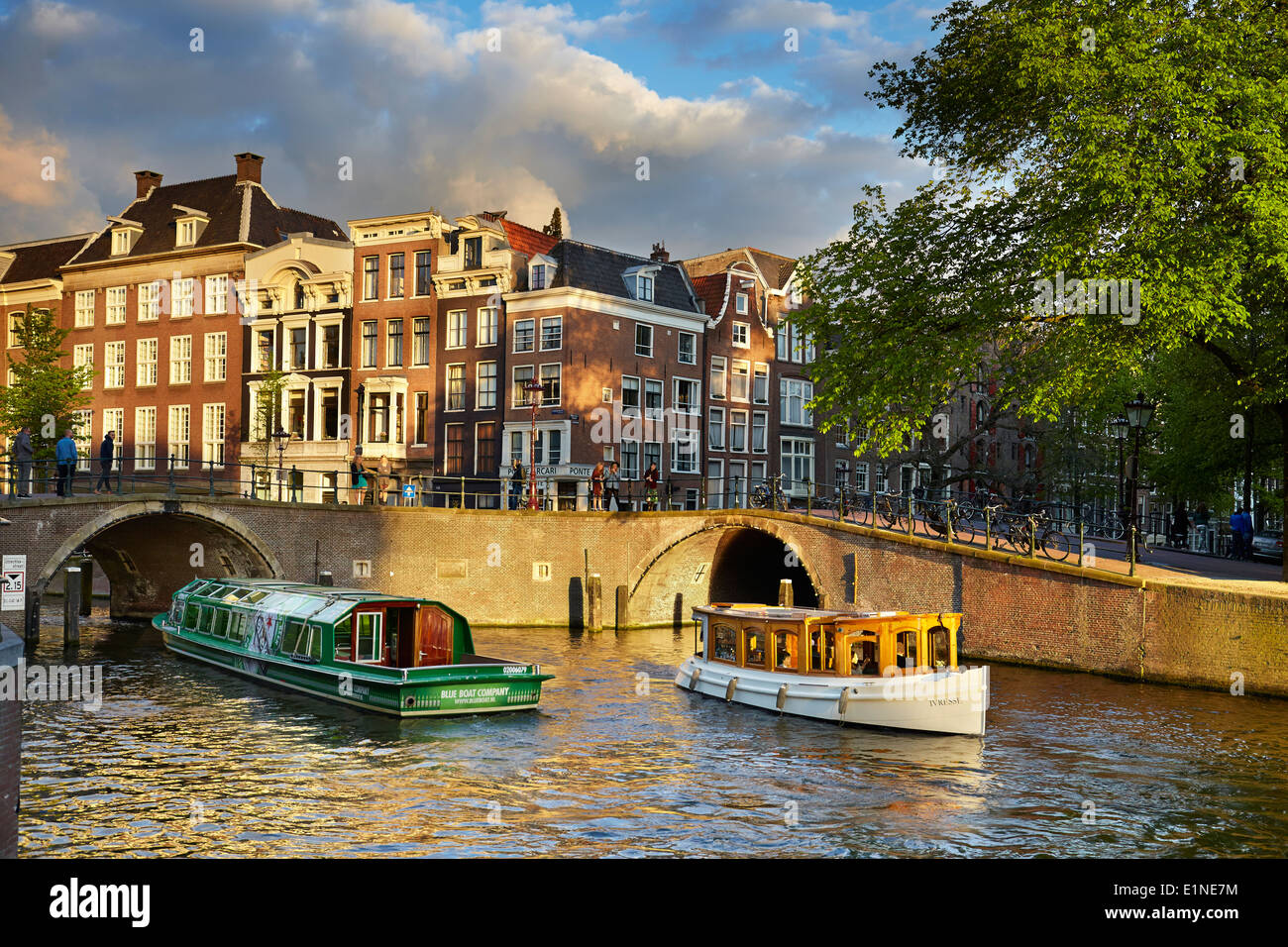 Tourist boat at Amsterdam bridge canal - Holland, Netherlands - Stock Image