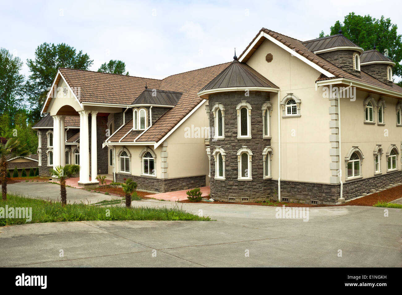Horizontal photo of brand new custom built home with palm trees in front and large front drive with trees and partly Stock Photo