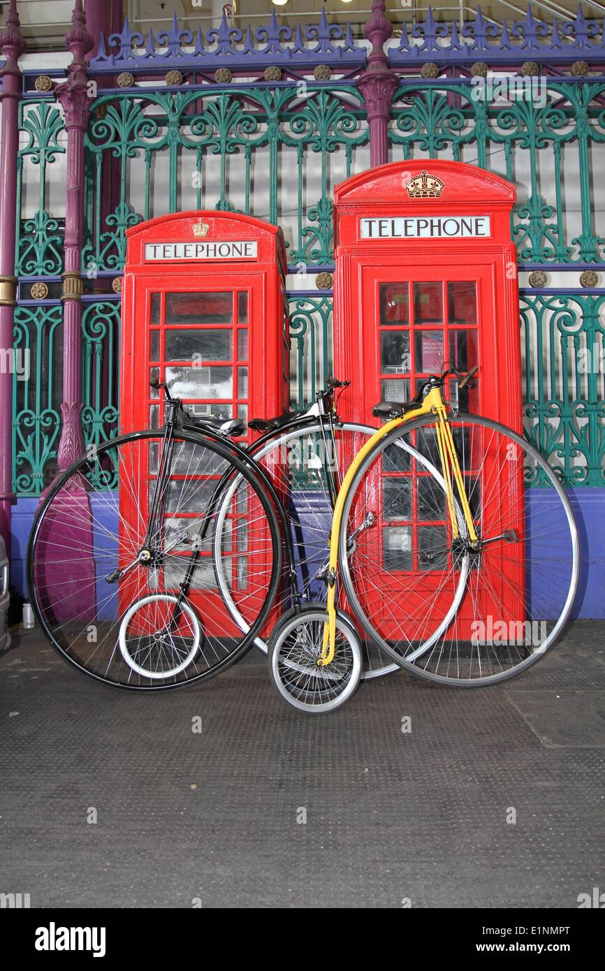 Smithfield Market, London, UK. 7th June 2014. London Nocturne cycling event. Penny Farthings leant against red telephone boxes in Smithfield Market Credit:  Neville Styles/Alamy Live News - Stock Image