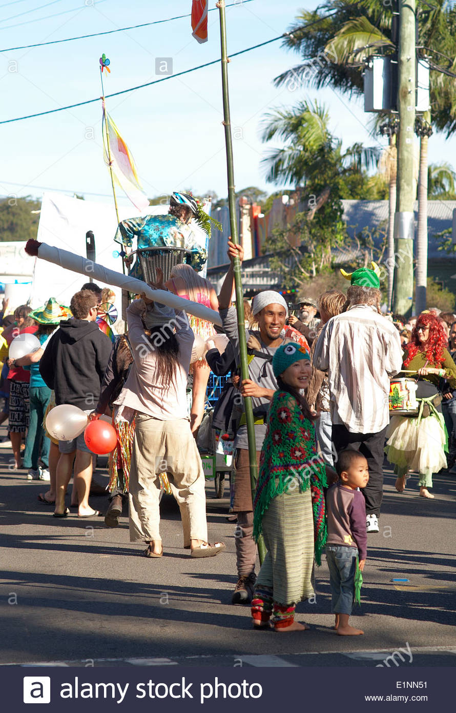 A young Japanese couple - the man holding a long bamboo flag - with their boy child, turn smiling, from the rear of the 2014 Nimbin Mardigrass parade. - Stock Image
