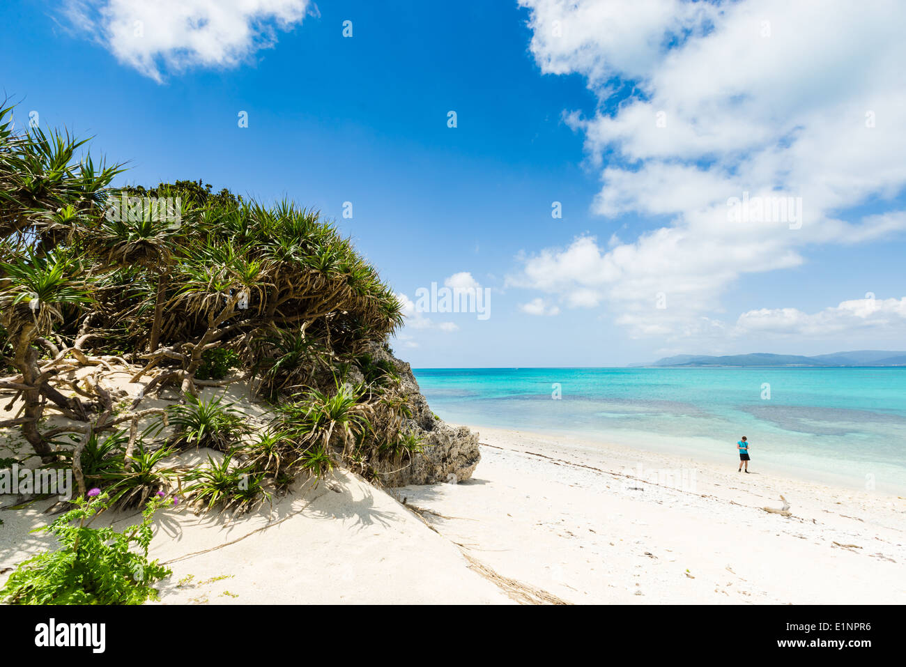 Man admiring perfect white sand beach surrounded by crystal clear tropical water of Okinawa, Japan - Stock Image