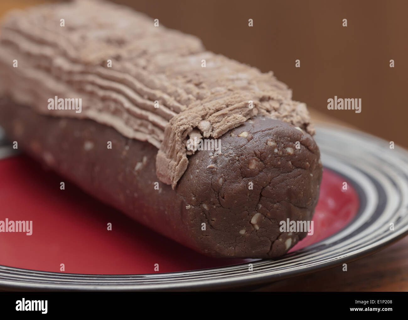 Chocolate dessert log ready-to-eat on red plate - Stock Image