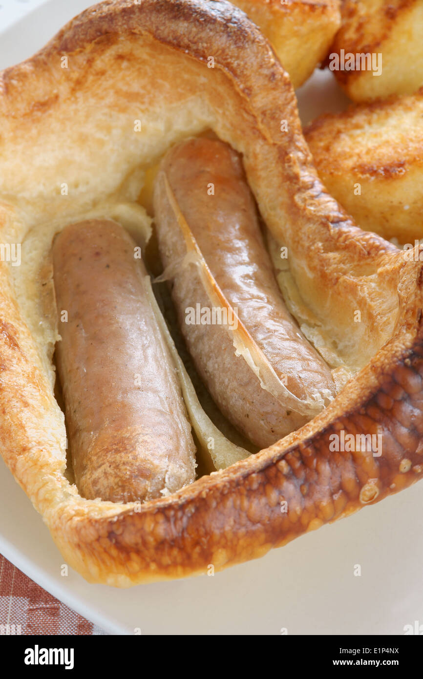 Toad in the Hole a British dish of sausages cooked in Yorkshire pudding - Stock Image