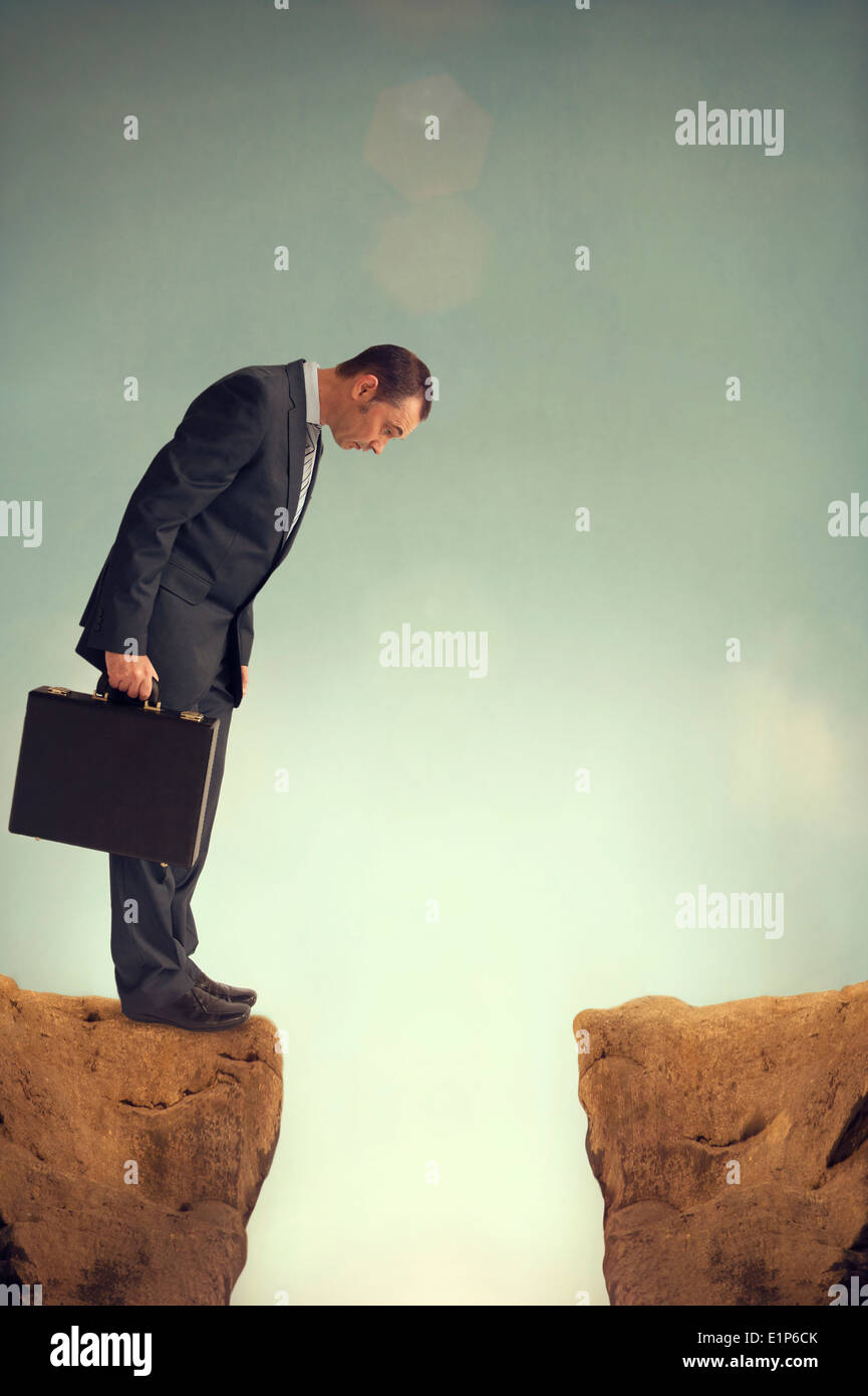 businessman on the edge of a ravine looking down at his predicament Stock Photo