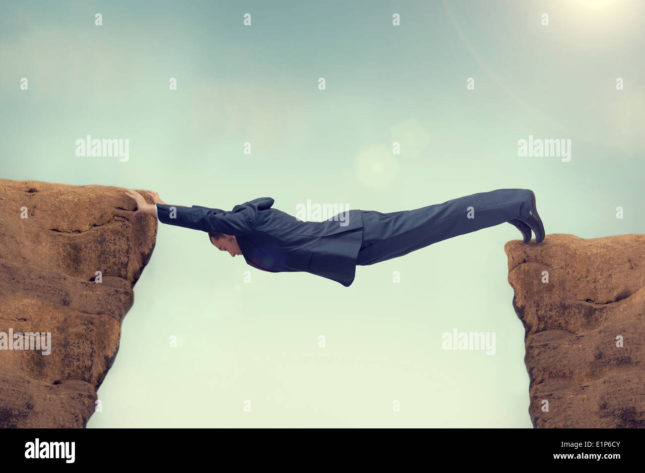 businessman overstretched between a rock and a hard place Stock Photo
