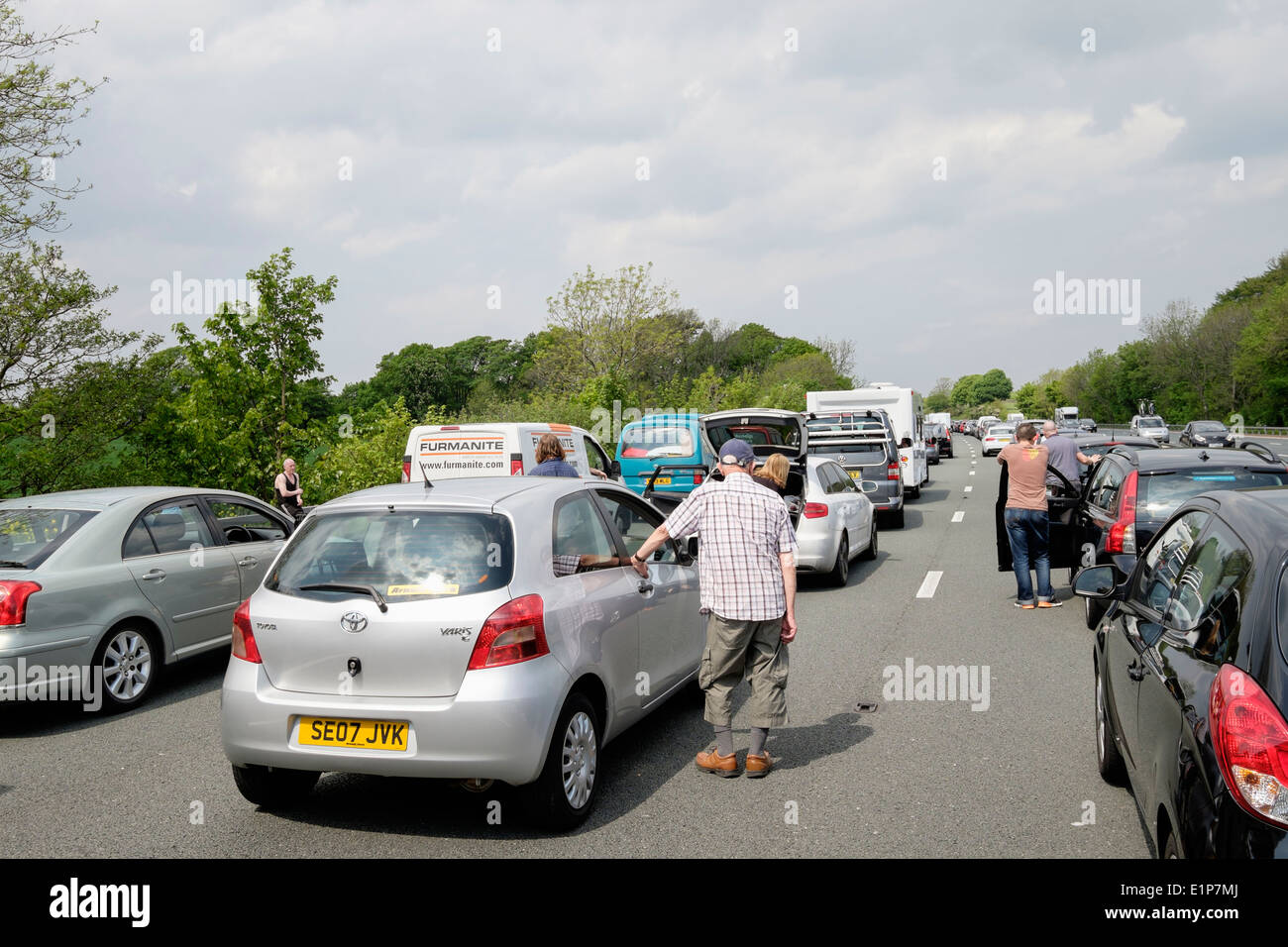 People standing on carriageway outside stationary vehicles in a traffic jam of cars on M6 due to accident causing Stock Photo